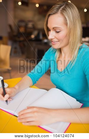 Close-up of happy young woman writing on book at table in cafe