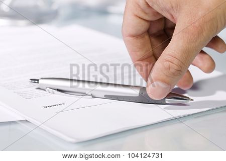 Close-up Of A Hand Taking A Pen To Fill And Sign Documents.