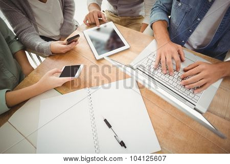 Mid section of business people using laptop and smartphones while sitting at desk