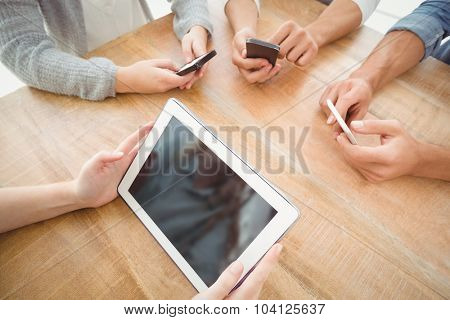 High angle view of cropped hands using smartphones and digital tablet at desk