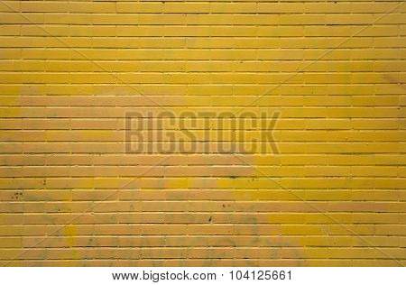 Yellow brick wall with faded graffitis