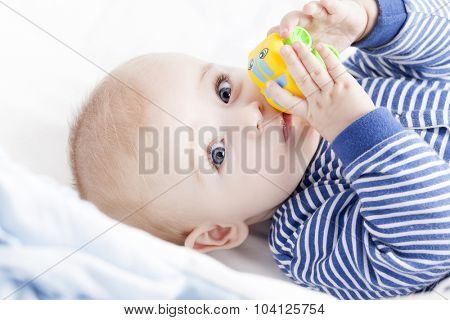 Baby with blue eyes playing with a toy