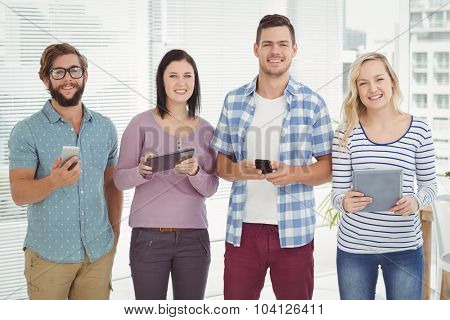 Portrait of smiling business people using electronic gadgets while standing at office