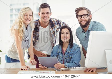 Portrait of smiling business professionals using digital tablet at desk in office