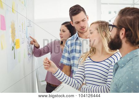 Business people talking while standing at wall with sticky notes and drawings in creative office