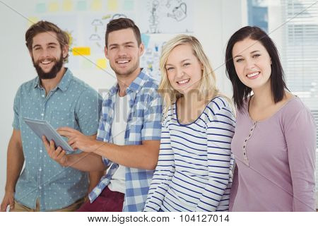 Portrait of smiling man holding digital tablet standing with coworkers at office