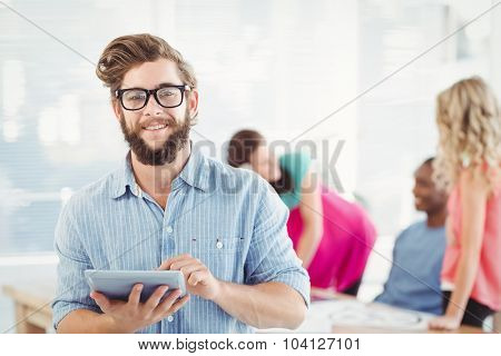 Portrait of smiling man wearing eyeglasses using digital tablet while standing at office