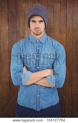 Portrait of serious hipster with arms crossed standing against wooden wall