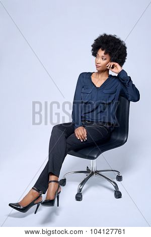 Portrait of confident black african business woman sitting on executive chair in studio, isolated on grey background