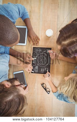 Close-up of people writing business terms on slate at table
