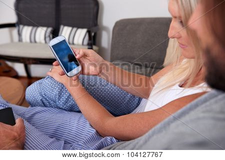 couple relaxing with mobile cellphones on sofa couch in home living room lounge