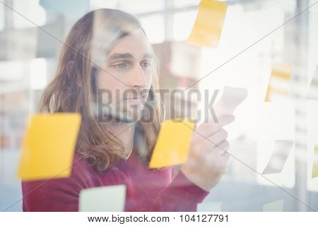 Businessman holding sticky note stuck on glass in office