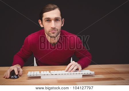 Portrait of confident creative businessman sitting at desk in off