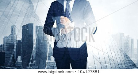 Double exposure of young business man in the skyscraper on background