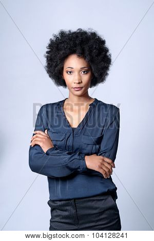 Confident self assured black african business woman with afro in studio, isolated on grey background