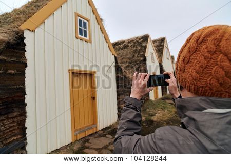 Woman taking picture with mobile cell phone of Traditional Icelandic Turf Houses in North Iceland