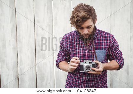 Hipster using camera against wooden fence