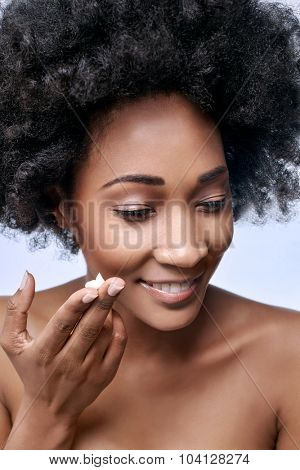 Beautiful black african model with moisturiser face cream on her fingers, beauty cosmetics skincare concept