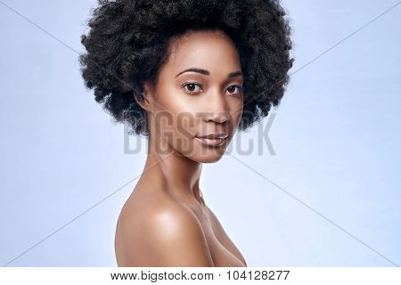 Headshot of attractive young black african model smiling in studio with smooth complexion flawless skin, skincare beauty cosmetics concept