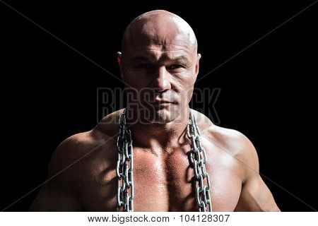 Portrait of confident muscular man with chain against black background
