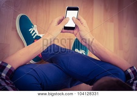 High angle view of hipster using smartphone while sitting on hardwood floor