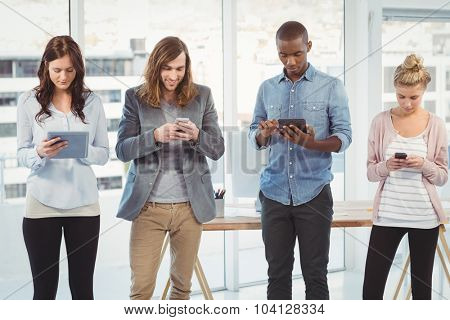 Business team using technology while standing at office