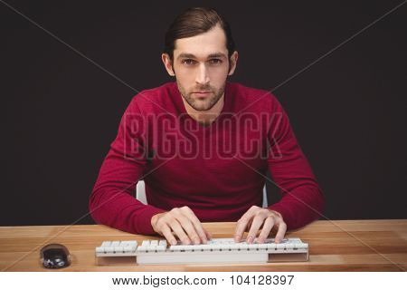 Portrait of serious man typing on keyboard at desk in office