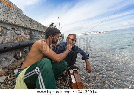 KOS, GREECE - SEP 27, 2015: Unidentified refugee shaves the other on the beach. Kos island is located just 4 kilometers from Turkish coast, and many refugees come from Turkey in an inflatable boats.