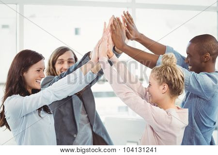Smiling business team giving high five at desk in office