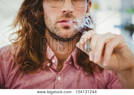 Mid section of hipster smoking electronic cigarette