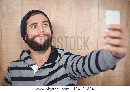Hipster making face while taking selfie on mobile phone against wooden wall