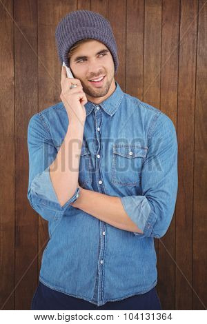 Happy hipster wearing knitted hat using mobile phone against wooden wall