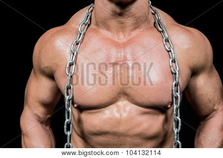 Midsection of muscular man with chain against black background