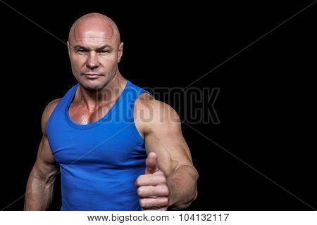 Portrait of confident muscular man showing thumbs up against black background