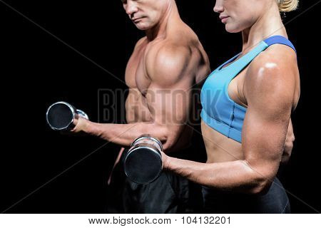 Midsection side view of man and woman lifting dumbbells against black background