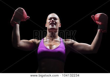 Winning woman cheering with arms raised against black background