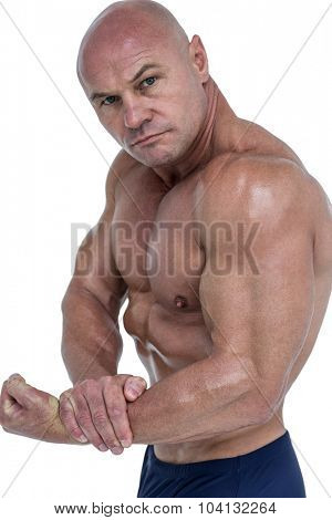 Portrait of man flexing muscles against white background