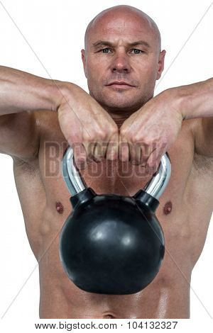 Portrait of confident man lifting kettlebell against white background