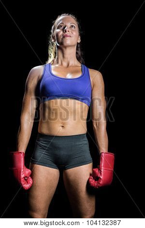 Female athlete standing with gloves against black background