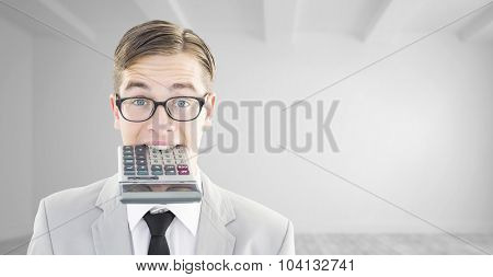 Geeky smiling businessman biting calculator against bright white room