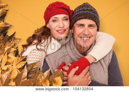 Happy couple in warm clothing against autumn leaves pattern