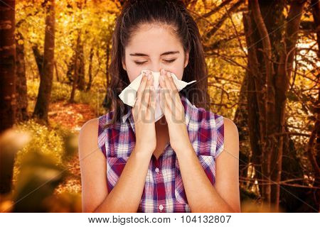 Beautiful woman sneezing in a tissue against tranquil autumn scene in forest