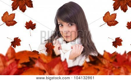 Brunette in winter clothes smiling at camera against autumn leaves