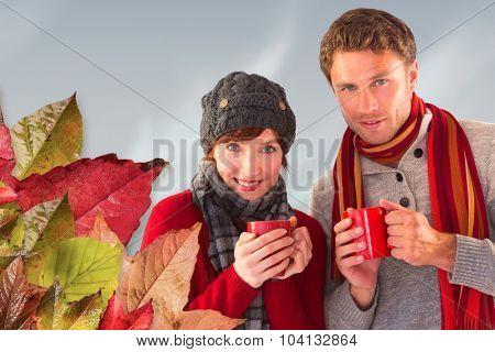 Couple both having warm drinks against blue sky