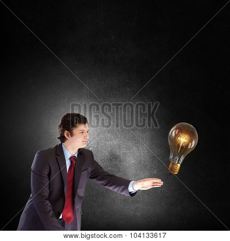 Businessman reaching hand to touch glass light bulb