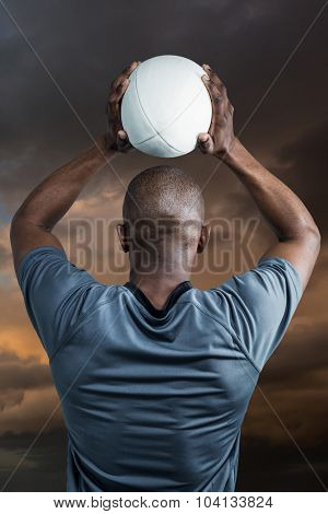 Rear view of athlete throwing rugby ball against blue and orange sky with clouds