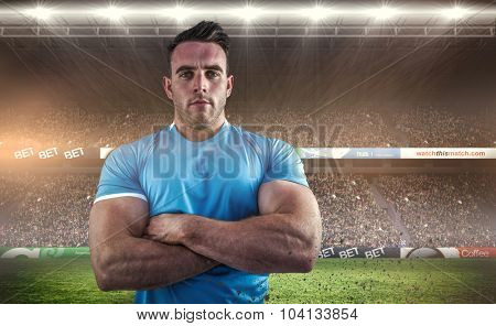 Rugby player looking at camera against rugby fans in arena