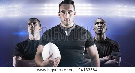 Tough rugby player holding ball against spotlights