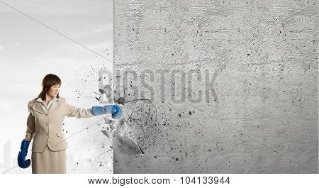 Young businesswoman in blue boxing gloves punching wall