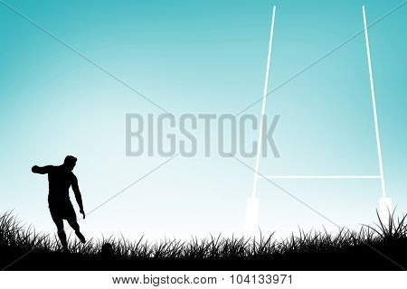Rugby player kicking the ball against blue vignette background
